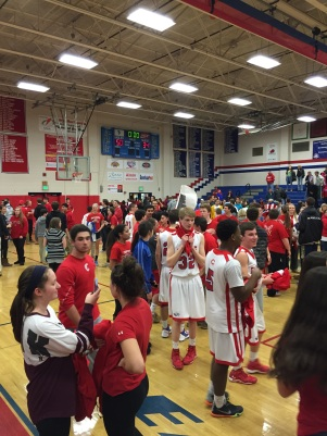 The fans flood the court to congratulate the team.
